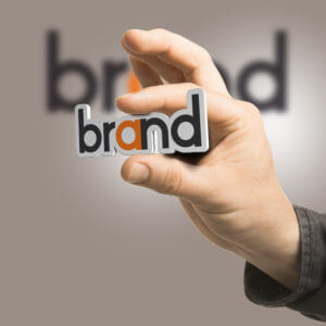 One hand holding the word brand over a beige background. Branding concept. The image is a composition between 2D illustration 3D rendering and photography